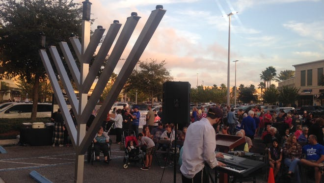 People gather to light the first candle on a giant menorah at the Avenue Viera shopping center on the first night of Hanukkah