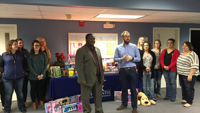 Mayor Mayo presents Center for Children and Families' Adam McDonald and staff with toy donation