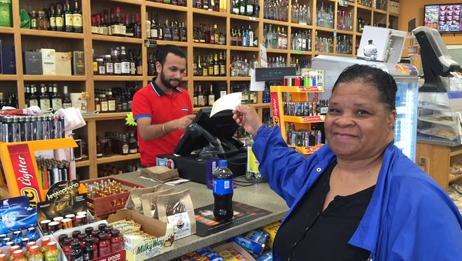 Betty Nete takes her Powerball ticket from cashier Rag Katwal.