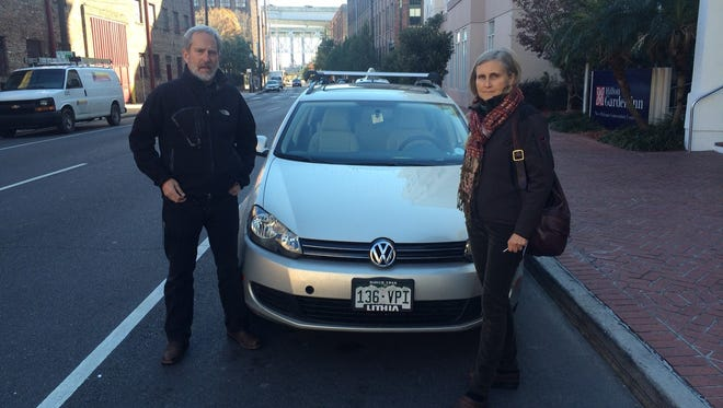 Marcus Moench and Elisabeth Caspari stand next to their 2011 Volkswagen Jetta SportWagen TDI in New Orleans. The couple from Boulder, Colo., are on a cross-country trip to protest the Volkswagen scandal. They are driving to the Volkswagen Group of America's headquarters in Herndon, Virginia.