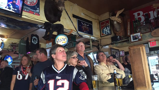 Football fans watch the AFC Championship football game between the New England Patriots and the Denver Broncos at The Pour House in South Burlington on Sunday.