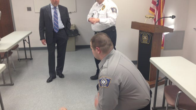 An EMT practices CPR on a dummy as Congressman Tom MacArthur (left) and Mount Laurel Emergency Medical Services Chief Joseph Stringfellow look on.