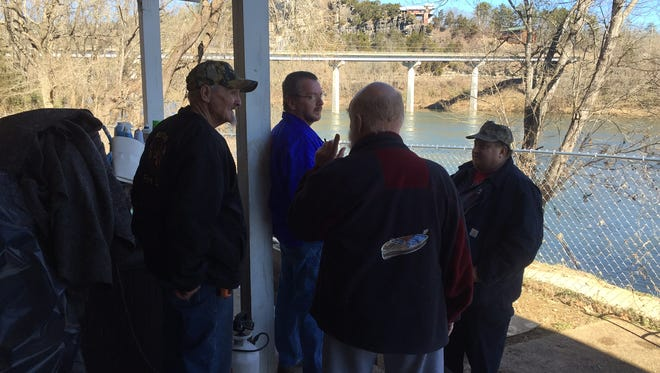 Members of the Norfork VFD talk after rescuing three men involved in a boating accident on the White River at the Sheid Bridge.