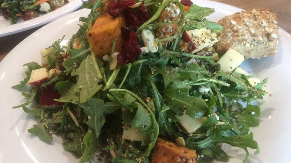 A Glorious Green Salad is heaped  with sweet potatoes, goat cheese, apples and other healthy fare.
