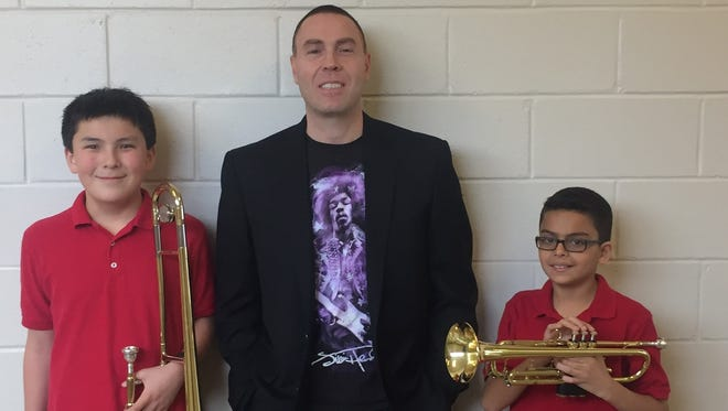 Trombonist Jonathan Choo (left) and trumpeter Adrian Ferrer, members of the Veterans Memorial Middle School band, qualified to perform with the All South Jersey Junior High Band. They are pictured with their band director, Ed Zatzariny.