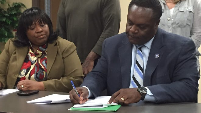 Southside Economic Development District President Augusta Turner watches as Monroe Mayor Jamie Mayo signs paperwork finalizing land acquisition of the U.S. 165 South Business Connector
