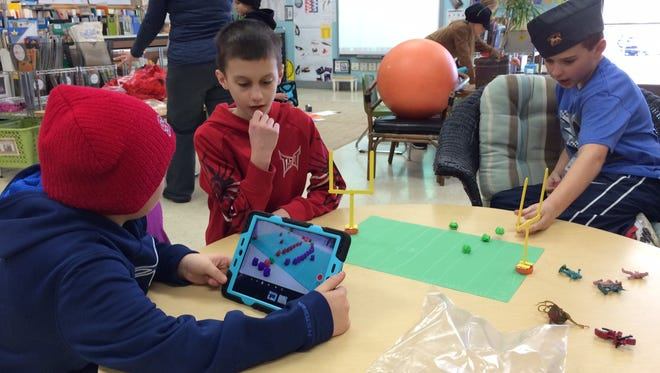 Fourth-grade students Noah Moll, left, Avery VanRemordel and Noah Rass spent Monday's tech club working on their football-themed stop-motion movie