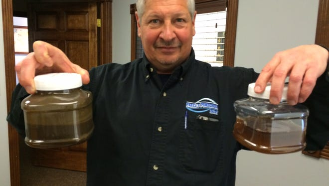 John Pagel displays liquid manure before (left) and after it has been processed to remove harmful nitrogen and phosphorus.