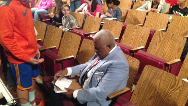 Eugene Richardson, a member of the famed Tuskegee Airmen, signs autographs for students before a presentation on Tuesday at Harrington Middle School.
