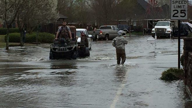 Trucks and ATVs make their way through a flooded portion of Frenchmen's Bend Subdivision Friday morning
