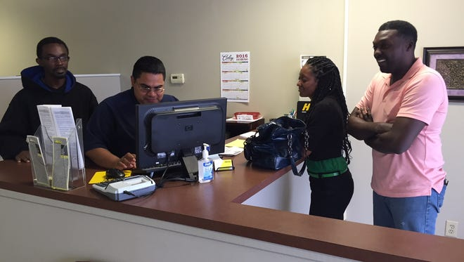 Filo Sharp (at computer) and Avery Holland (at left) assist customers at Hertz Rental Car in Monroe.