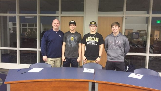 (From left to right) Marysville head coach Mark Caza, Alex Mugridge, Dan Bell and Travis Disser pose after signing to their future colleges.