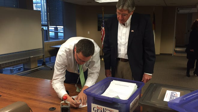 Jeff Mustin, left, of the Colorado Secretary of State's office, signs in Jack Graham and the delivery of his petitions to be on the June Republican primary ballot for U.S. Senate.