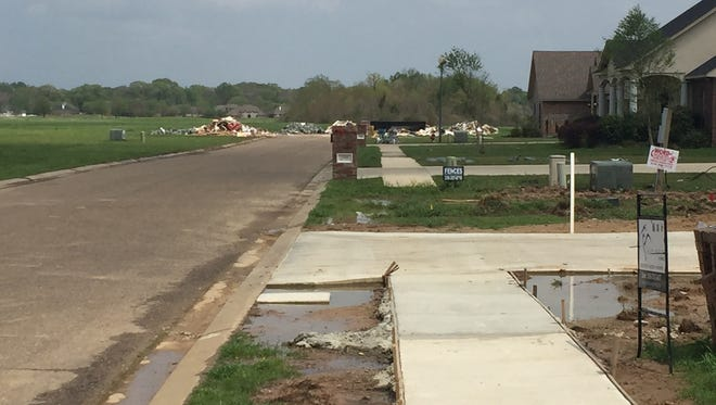 New and recent houses lead to a cu-de-sac with debris on Bunker Lane in Frenchman's Bend.
