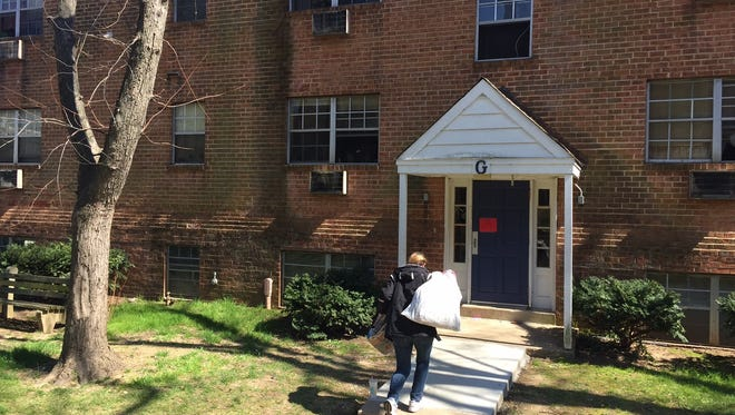 A woman walks into a building in the Riverfront Heights apartment complex, where four people died, likely due to a faulty boiler exhaust pipe on March 25.
