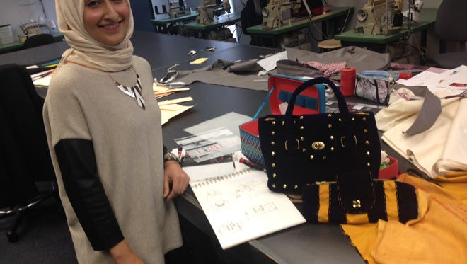 Rowan College at Burlington County student designer Insia Malik of Marlton stands next to a purse she made for a Power of the Purse event for the American Red Cross of Southern New Jersey.