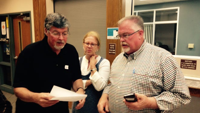 Van Smith, right, his wife, Fran, and Robert Young go over election results Tuesday night.