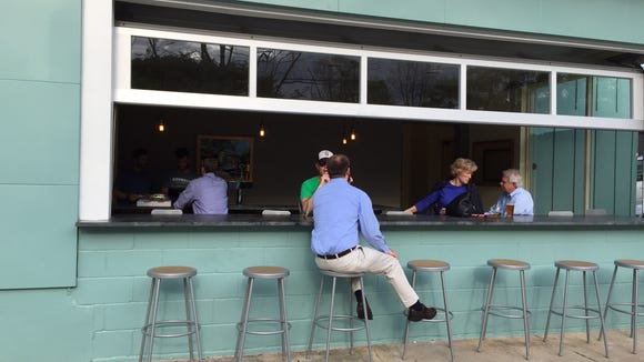 "An ""indoor-outdoor  bar"" allows for seating on either side of a wall with a roll up garage door."