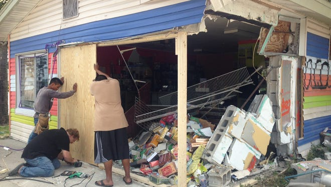 Workers shore up the corner of a building on Palm Beach Boulevard severely damaged when a car crashed into it Sunday morning. One person in the car was killed.