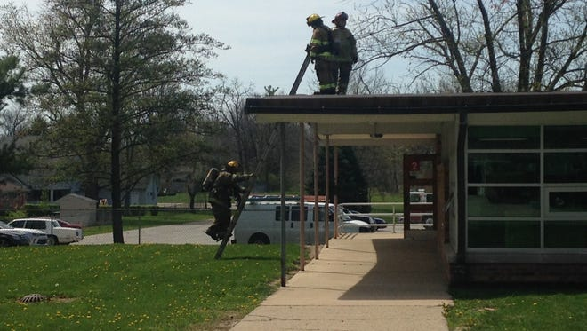Firefighters check the roof at West View Elementary School looking for the source of smoke that prompted a brief evacuation of the school Monday morning.