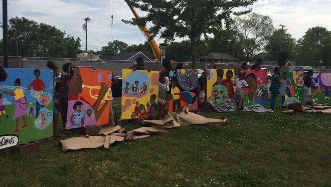 Youth from the Cheatham Place public housing complex unveiled their finished public art project Wednesday, which will be displayed on Jefferson Street.