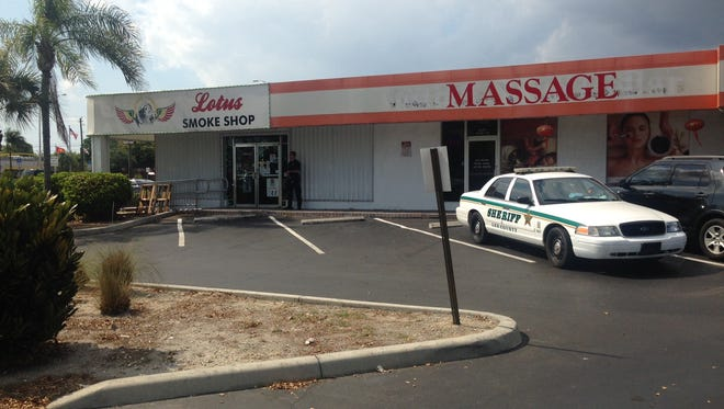A Lee County sheriff's deputy stands guard outside a Fort Myers smoke shop after a raid.