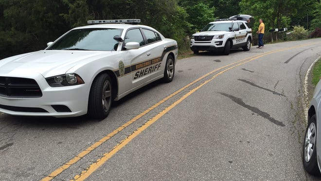 Sheriff's cars are parked near the entrance of Camp Creek Drive in Candler.