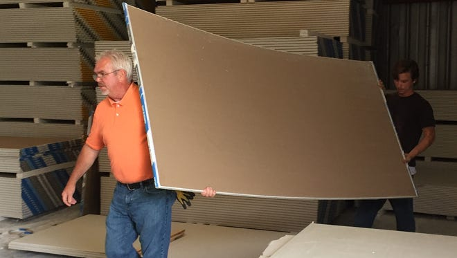 Tommy Younse and B.J. Jordan carry sheetrock to a customer's truck at Tom Sander Building Mart in West Monroe.