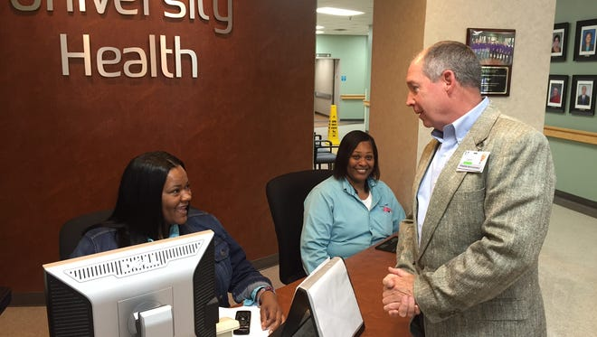 University Health Conway Hospital Administrator Larry Donner spends a moment talking with front desk operators Wednesday afternoon.