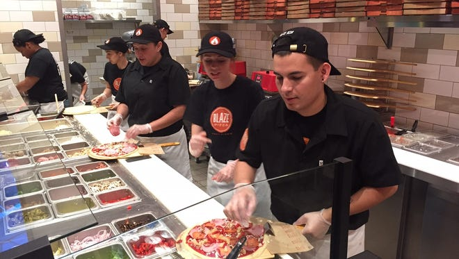 Blaze crew prepare pizzas as they prepare for free pizza day Friday in Visalia.