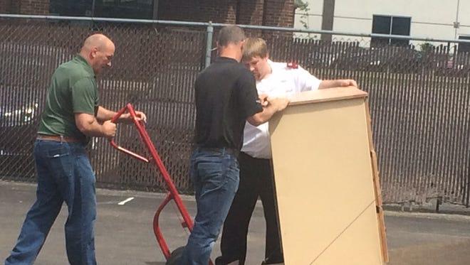 Kyle Olund, left, assists Matt Spink, black shirt and Jacob Tripp.
