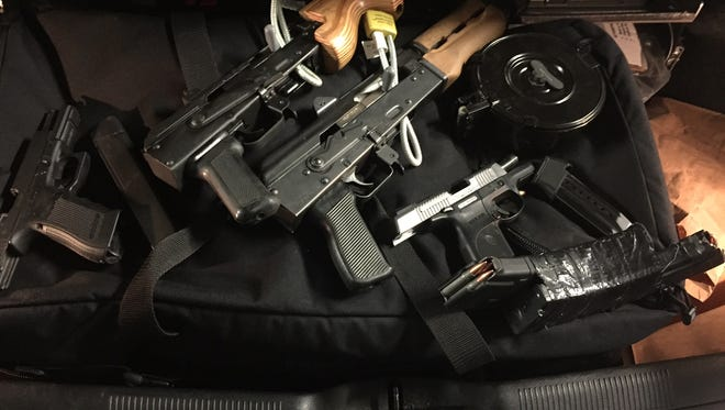 Four guns were found at a Troy traffic stop after the driver was reported pointing two out an SUV window.