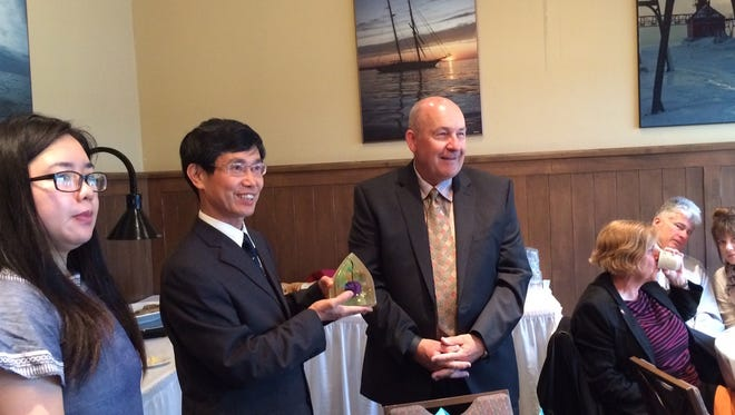 "During a breakfast at Stone Harbor Resort and Conference Center in Sturgeon Bay on Monday, Door County Board Chairman David Lienau, right, presents Hu Zhirong (center), vice mayor of Jingdezhen, China, with a gift from Popelka Trenchard Glass. Hu Zhirong, who is part of the Jingdezhen Sister City delegation, presented officials with a white and blue plate baring the words ""Jingdezhen Sister City Delegation of China."" Underneath are the words ""Door County."" Also pictured is translator Jiou Lin."