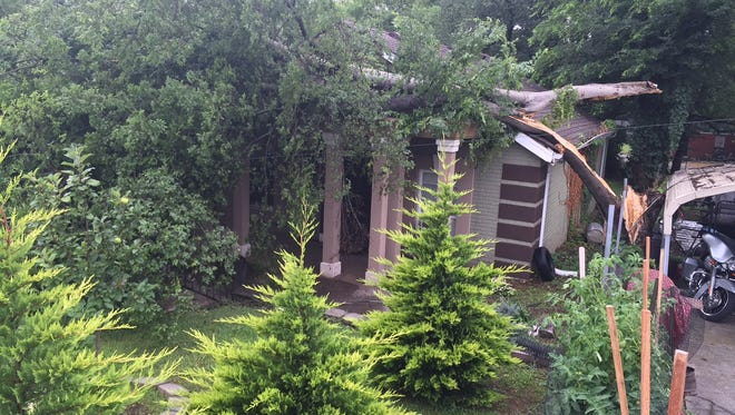 A tree lays across a home at 38th Avenue North after storms blew through Nashville Thursday night.