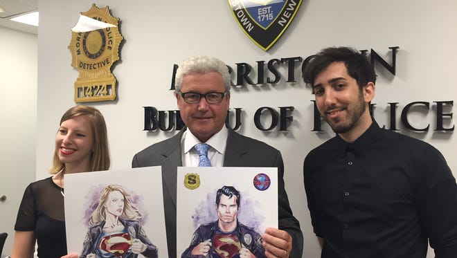 From left, artist Bella Rachlin, Morristown Mayor Timothy Dougherty and artist Idan Knafo Kerbis display watercolor depictions of Supergirl and Superman created by the artists. Prints will be given out at the Garden State Comic Fest by Morristown police on July 9-10, 2016.