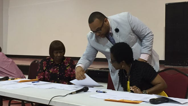 Richwood Mayor Gerald Brown provides board members Leola Keys (left) and Janice Fleming with applications for clerk of court during Thursday's meeting.