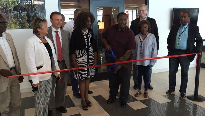 Monroe Mayor Jamie Mayo prepares to cut the ribbon in opening the Bayou Room Airport Lounge at the Monroe Regional Airport.