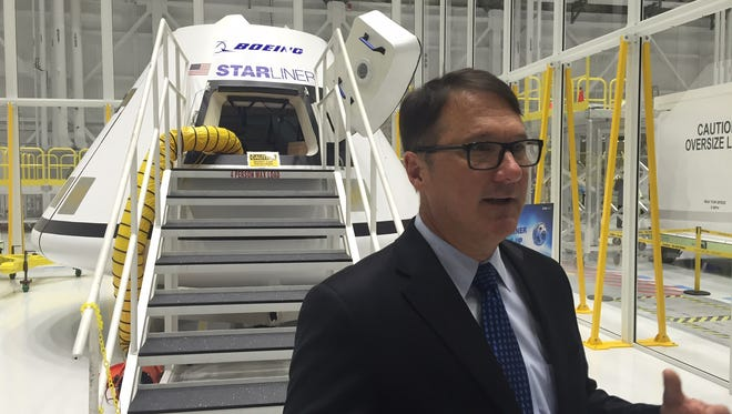 John Mulholland, vice president and program manager of Boeing Commercial Programs, on Tuesday discussed development of the company's CST-100 Starliner crew capsule inside a renovated former shuttle hangar at Kennedy Space Center.
