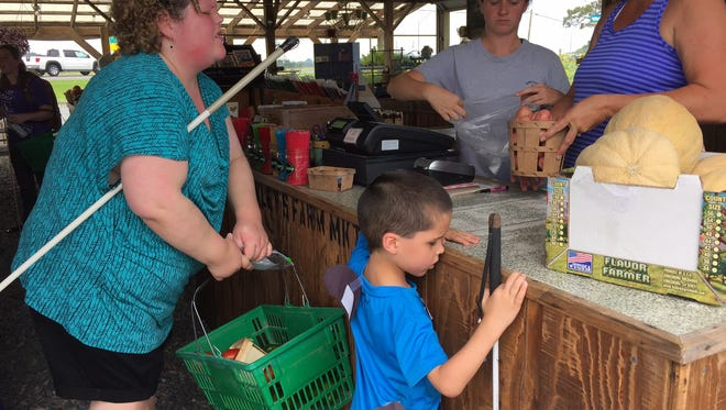 In this July 28, 2016 photo, Alycia Breitschwerdt, an independent living instructor at the Blind Industries rehabilitation facility in Salisbury, helps a 6-year-old boy named Aaron shop for produce at Oakley's Market in Hebron. Aaron participated last week in a summer enrichment and education program for blind and low-vision children. Breitschwerdt also is blind or visually impaired.