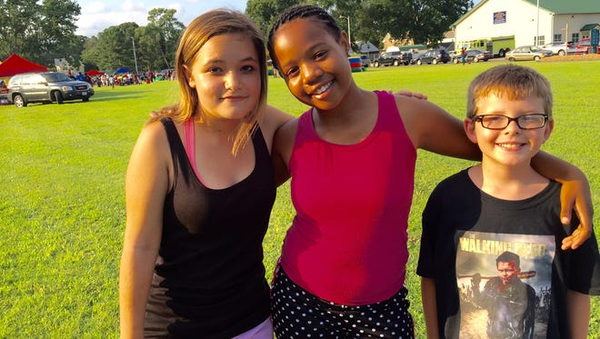 In this Aug. 2, 2016 photo, Somerset Intermediate School students from left, Cameron Abbott, 12, Serenity Polk, 11, and A.J. Abbott, 12 hang out at the annual National Night Out in Princess Anne where segments of the community joined members of allied law enforcement agencies promoting partnerships and camaraderie.