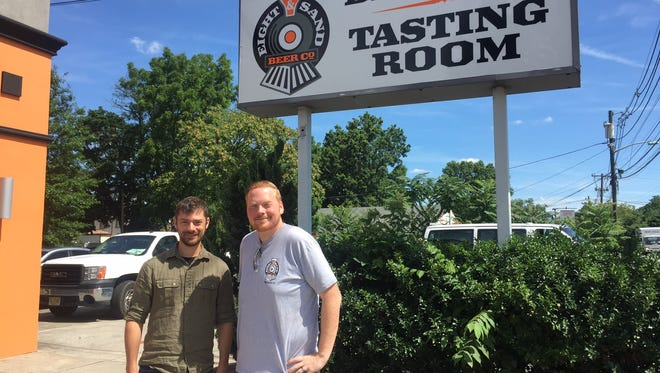Chris Mazzone (left) and Chris Burke stand outside beneath the sign for Eight & Sand Beer Company's brewery and tasting room. It will have its official opening on Friday.