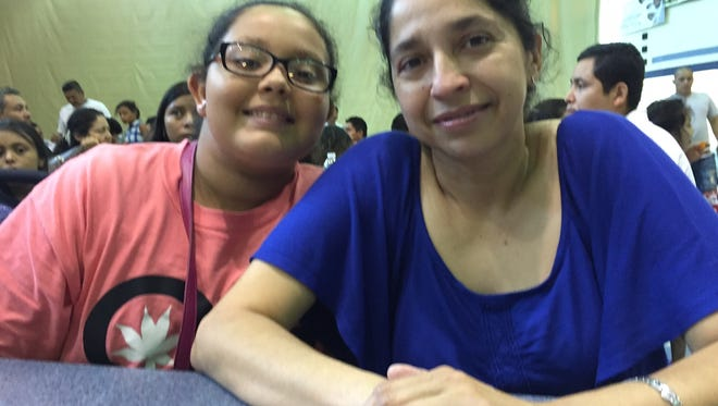 Doris Rogue, 43, waits with her daughter, Carlissa, 12, Saturday morning for a MARCC ID card.