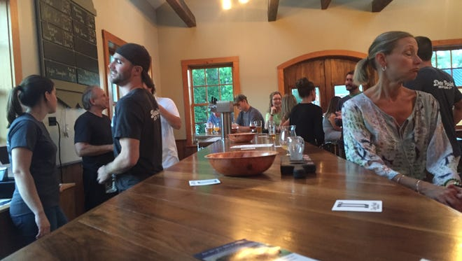 Patrons take in the first batches of Dew Point Brewing Co.'s creations in Yorklyn Friday.
