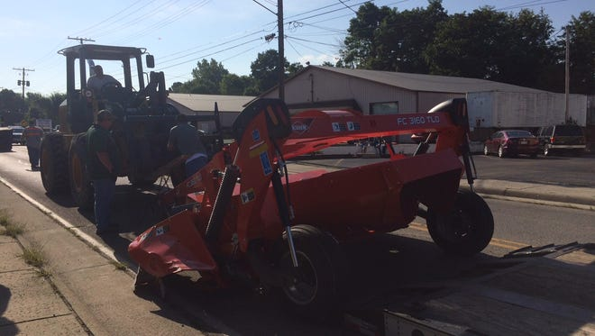 Crews work to remove farm equipment from the road that was struck by a car along Cedar Hill Road on Friday.
