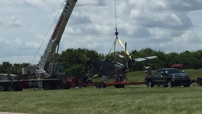 A crew uses a crane to remove the wreckage of a crashed Sikorsky S-61N helicopter at the Compound in Palm Bay on Wednesday (September 7).
