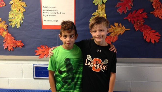 Lucas Costa-Carlos (left) stands next to his Van Zant Elementary School fifth-grade classmate Cameron McAndrew (right). Lucas performed the Heimlich maneuver on Cameron last month during lunch period when Cameron began to choke on his food.