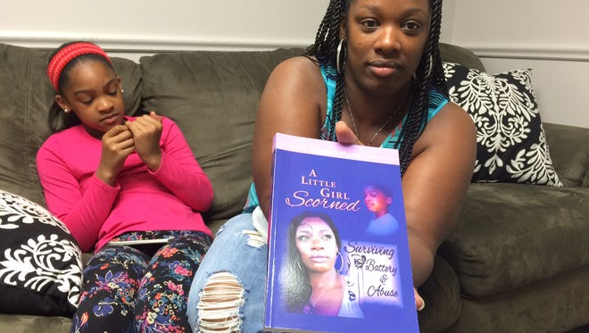 Debreka Handy with her daughter Rickalya Jones, 11, shows off her new book about surviving abuse.