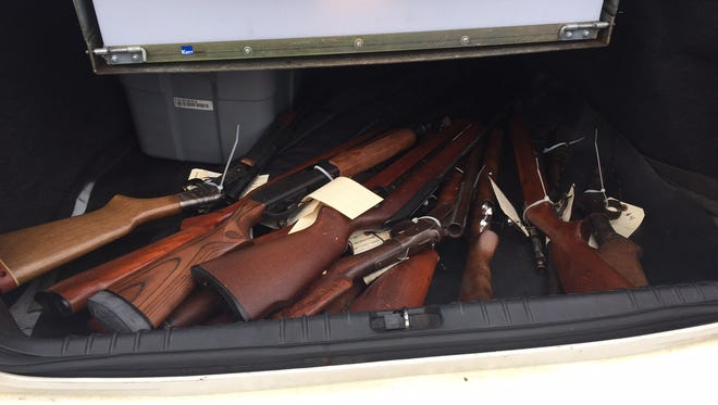 Firearms from a community gun buyback Saturday, Oct. 29, 2016, are placed in a police car for disposal.