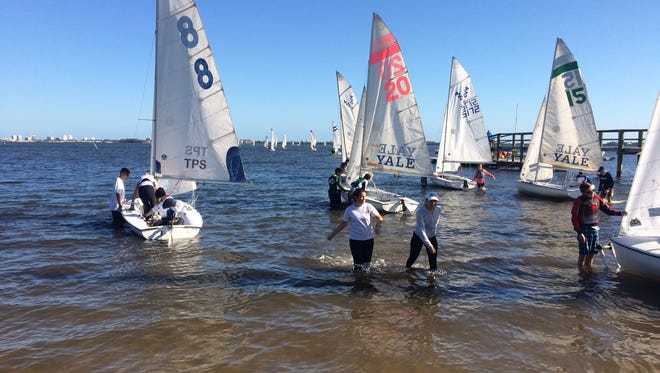 High school sailors including Holly Gandolfo (left center) and Virginia Zedda (right center), both of the Vero Beach High School sailing team,  prepare race last weekend at the SAISA points regatta in Jensen Beach.