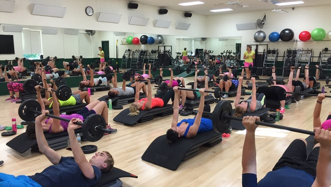 Bodypump class participants reap the benefits of resistance training by lifting light weights with many repetitions.